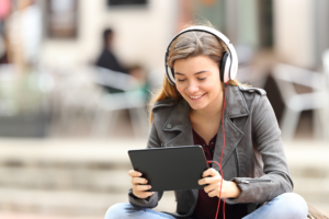 Young woman smiling at a tablet device with headphones on